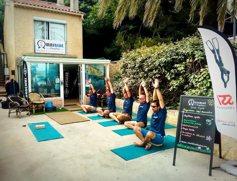 Ecole d'apnée omniblue avec 5 stagiaires faisant du stretching sur des tapis de yoga de qualité